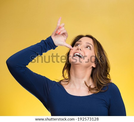 Closeup portrait young, silly, goofy woman, gesturing with hand thumb to go party, get drunk, hammered, wasted, isolated yellow background. Positive emotions, facial expressions, feeling, sign, symbol - stock photo