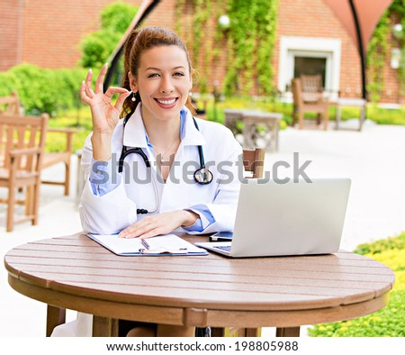 Closeup portrait, young smiling confident female doctor with stethoscope healthcare professional giving ok sign gesture isolated background hospital campus. Patient visit health care. Positive emotion - stock photo