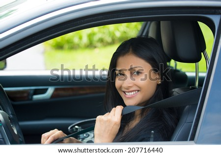 Closeup portrait young smiling, happy, attractive woman pulling on seatbelt inside black car. Driving safety, buckle up to prevent traffic death from accidents concept. Life-saving measures - stock photo