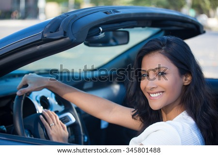 Closeup portrait young smiling, happy, attractive woman smiling from behind in her brand new sports car drop top, hand on steering wheel, isolated outdoors background  - stock photo