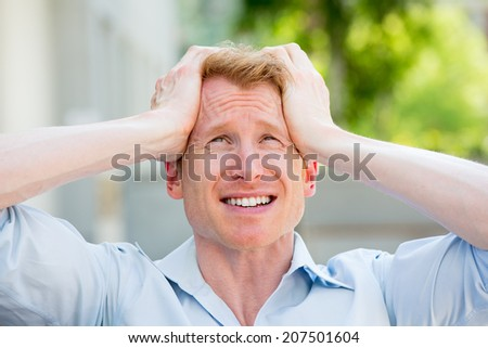 Closeup portrait, young stressed man in blue shirt with hands on temples, head about to explode, almost having nuclear meltdown, isolated outdoors, outside background - stock photo