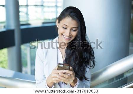 Closeup portrait, young successful happy business woman in light white gray suit, checking her cellphone, isolated on interior indoors office background . Business communication - stock photo