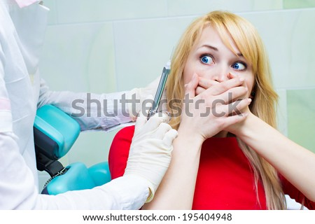 Closeup portrait young terrified girl woman scared at dentist visit, siting in chair, covering her mouth, doesn't want dental procedure, drilling, tooth extraction, isolated clinic office background - stock photo