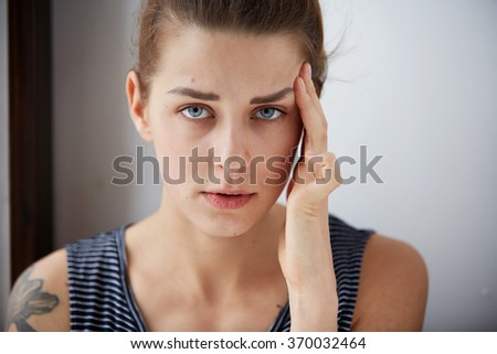 Closeup portrait young upset sad woman thinking deeply about something with headache holding her hands on head looking stressed isolated on gray wall background. Negative human facial expression - stock photo