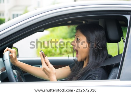 Closeup portrait, young woman driving in black car and checking her phone, then shocked almost about ot have traffic accident, isolated outdoors background - stock photo