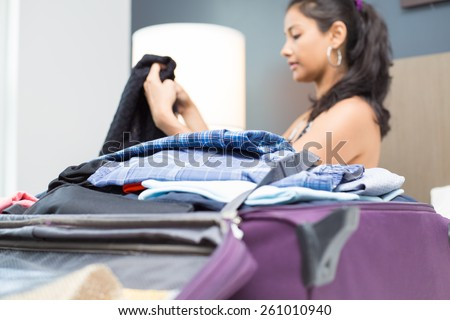 Closeup portrait, young woman folding clothes and placing inside maroon luggage, isolated indoors background on bed - stock photo