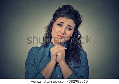 Closeup portrait young woman gesturing with clasped hands, please forgive me pretty please with sugar on top isolated gray background. Human emotion facial expression feeling sign symbol body language - stock photo