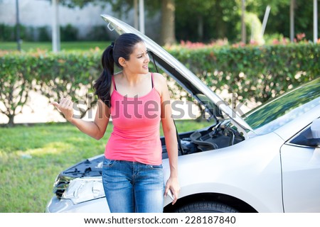 Closeup portrait, young woman in pink tanktop having trouble with her broken car, opening hood and putting out thumb to hitchhike, isolated green trees and shrubs outside background - stock photo