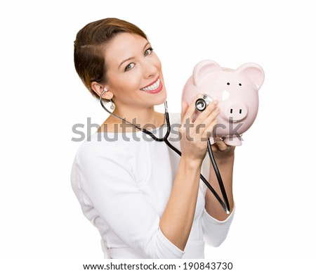 Closeup portrait young woman listening to piggy bank with stethoscope. Medical insurance, medicare reimbursement. Curious nurse, doctor, patient or business lady. Health law coverage, company report - stock photo