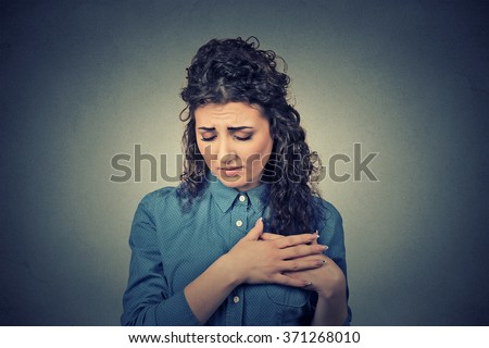 Closeup portrait young woman with breast pain touching chest isolated on gray wall background - stock photo