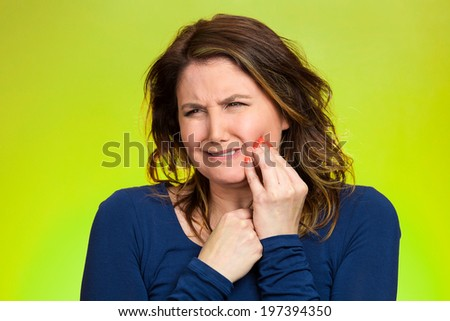 Closeup portrait young woman with sensitive tooth ache, crown problem crying from pain, touching outside mouth with hand isolated green background. Negative emotion, facial expression feeling, health - stock photo