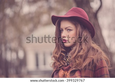 Closeup portraits of a beautiful european girl in a pink hat in a retro style with a professional makeup and bright lipstick, emotions, vintage in the winter park