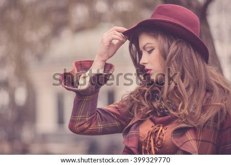 Closeup portraits of a beautiful european girl in a pink hat in a retro style with a professional makeup and bright lipstick, emotions, vintage in the winter park - stock photo