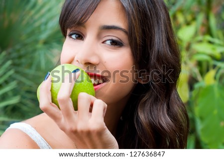 Closeup potrait of young woman holding a green apple