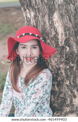 Closeup pretty woman wear red hat has beautiful smile under tree in the park vintage style,film tone,pastel