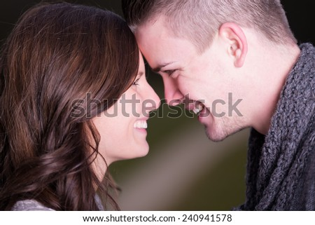 Closeup profile image of happy young couple looking face to face at eachother