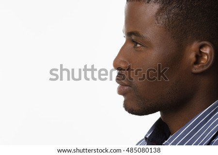 Closeup profile of Afro-American man smiling and looking away while posing over white background in studio.