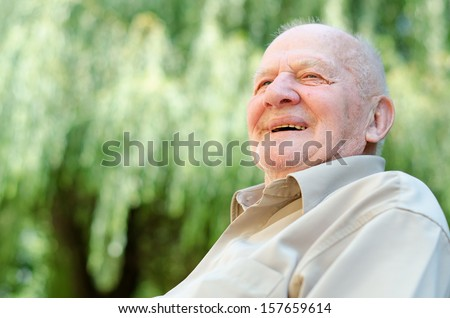 Closeup profile on a smiling old man - stock photo