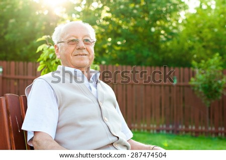 Closeup profile on a smiling old man sitting - stock photo