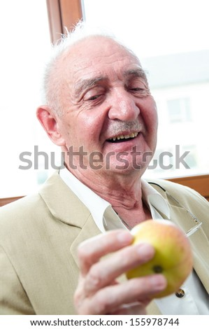 Closeup profile on a smiling old man with apple - stock photo