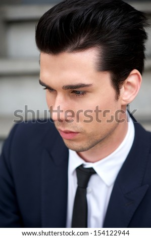 Closeup profile portrait of a handsome young man in suit and tie - stock photo