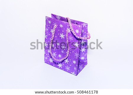Closeup purple new year gift bag with shiny snowflakes.View on top