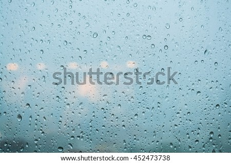 Closeup Rain drops on window glass against city background and refection of lighting inside a building. Summer rainy day. Detail natural of rain drops or abstract background. - stock photo
