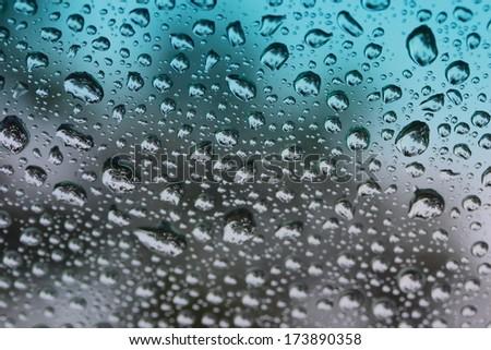 Closeup raindrops on Tinted glass - stock photo