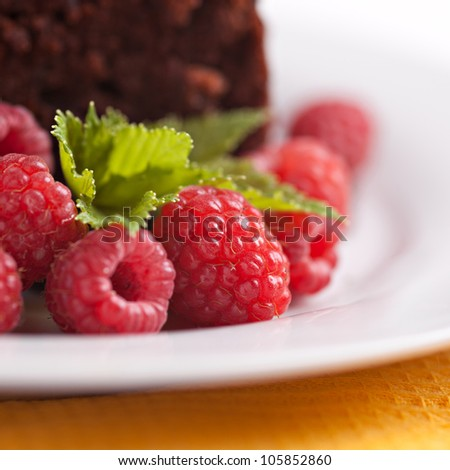 Closeup rapsberries on plate with chocolate cake