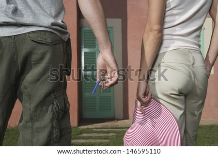 Closeup rear view midsection of man and woman in front of house with keys and hat - stock photo