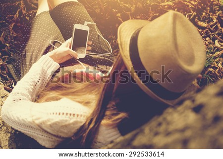 Closeup rear view of young woman in crochet blouse and skirt sitting next to a tree in autumn afternoon using smartphone texting. Horizontal, mild retouch, warm tones. - stock photo