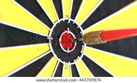 closeup red and green dart arrow hitting in target bullseye of a dartboard, business solutions, and success concept - stock photo