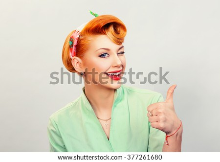 Closeup red head young woman pretty pinup girl green button shirt giving thumbs up sign gesture looking at you camera isolated white background retro vintage 50's style. Human emotions body language - stock photo