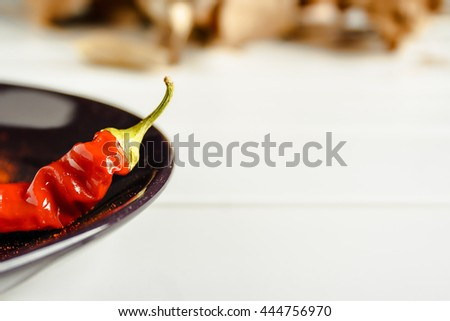 Closeup red pepper on brown dish over white wood. Horizontal image.