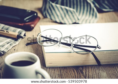 closeup round frame style of eyeglasses on wooden desk, shallow depth of field and filtered
