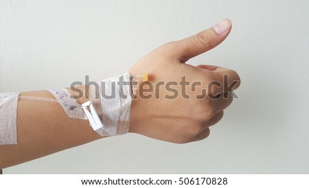 Closeup saline water line at the hand of patient  in hospital room, infusion line in a patients hand