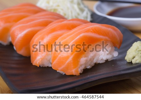 CloseUp Salmon sushi on a black plate. With wasabi and shoyu sauce. Placed on a wooden table. Focus salmon sushi. A highlight and blurring some light on the background.