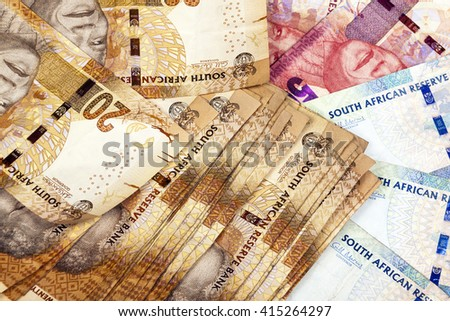 Closeup scattered collection of used South African twenty fifty and hundred Rand brown red and blue bank notes