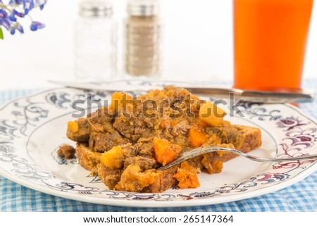 Closeup selective focus shallow depth of field on bite of beef stew over whole grain toast in country kitchen setting with sweet iced tea and blue gingham tablecloth.  Bluebonnet flower for decoration - stock photo