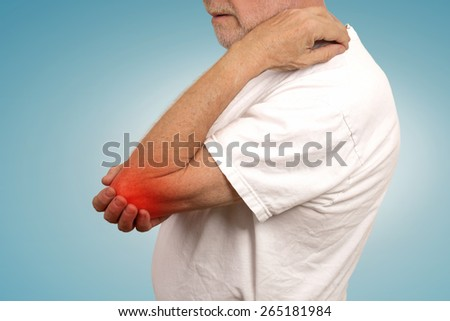 Closeup senior man with elbow inflammation colored in red suffering from pain and rheumatism isolated on bright blue background  - stock photo