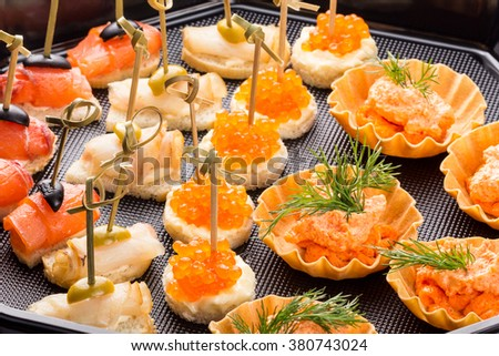 closeup set different canapes and snacks in plastic black form for mobile catering