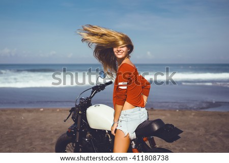 Closeup sexy back in jeans shorts of young pretty blonde woman sitting on vintage custom motorcycle traveling and having fun, hair dresser, crazy woman, posing near ocean, beach bali - stock photo