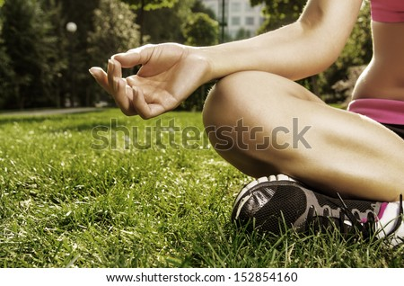 Closeup shoot. Hand of young caucasian woman sitting in lotus pose in the park - stock photo