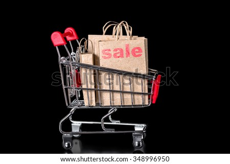 closeup shopping cart with sale paper bags is isolated on black background - stock photo