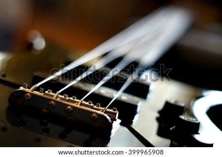 Closeup shot of a bass guitar bridge - Fender Jazz Bass style bridge. - stock photo