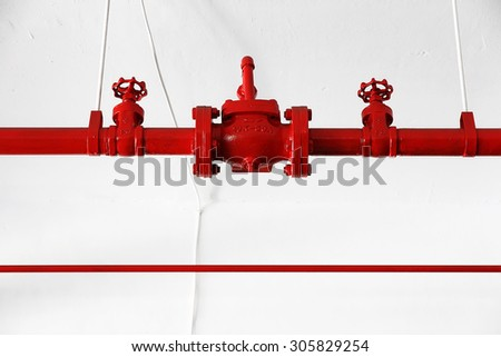 Closeup shot of a fire hydrant pump system consisting of steel pipes painted red against isolated white wall - stock photo
