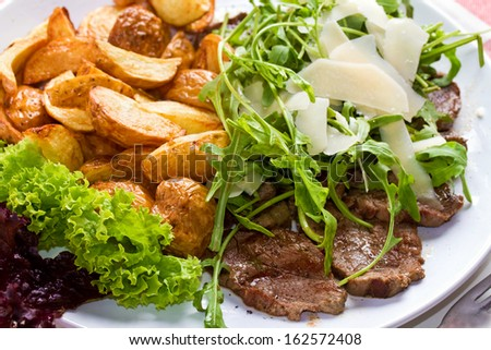 Closeup shot of a flank steak with fries and lots of leafy greens