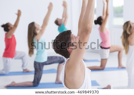 Closeup shot of a man with raised hands with yoga group in the background