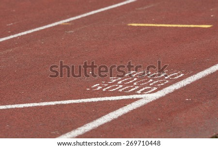 Closeup shot of a running track showing the race lengths. - stock photo