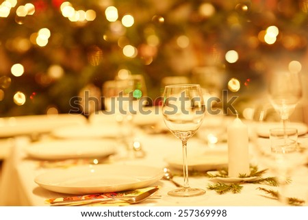 Closeup shot of a table set with glassware, plates and cutlery for a Christmas dinner - stock photo